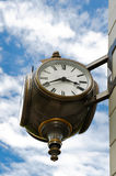 Street Clock. A municipal street clock in a town square photographed against a cloudy blue sky Royalty Free Stock Photography