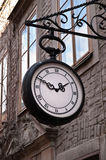 Street clock. Old city street clock on a house wall Stock Image