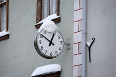 Street clock. Closeup of big round street clock covered with snow hanging on the wall Stock Photo