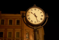 Street clock. At night time against blurry building Royalty Free Stock Photo
