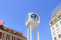 Street clock against the sky. Street clock against the sky and roofs of buildings Royalty Free Stock Image
