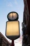 Street clock and blank advertising billboard. Illuminated round street clock and blank advertising billboard in evening Stock Images