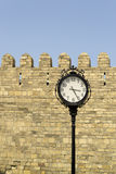 Street clock in front of castle wall Royalty Free Stock Photos