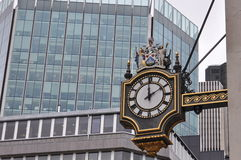 Street clock. London. Street clock decorated with Roman numerals decorated with figurs Royalty Free Stock Photo
