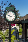 Street clock twelve to ten. Street clock against blue sky with trees and plants Royalty Free Stock Photo