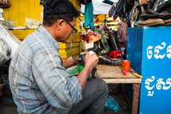 Phnom Penh, Cambodia - December 7, 2018. A street cobbler works on shoes. This street cobbler works on the footpath fixing shoes for anyone who needs work done stock photos