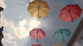Multicolored umbrellas soar in the sky