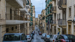 Street with colorful balconies in historical part of Valletta in Malta Stock Images