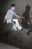 Street competition. Jumping boy in front of a graffiti wall stock images
