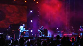 at a street concert of rock music, musicians sing on stage, fans dance and clap stock video