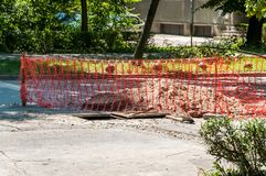 Street construction and reconstruction site with orange safety net or barrier over the open manhole in the asphalt Royalty Free Stock Photo