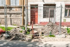 Street construction or reconstruction site of pipeline with metal industrial fence around the hole.  stock images
