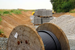 Street construction site. A view of a construction site where a new street is being built.  Image includes piles of subsurface gravel, a spool of coax cable and Royalty Free Stock Photography