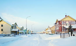 Street with cottages in the winter village Stock Images