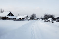 Street covered with snow in traditional russian village Stock Image