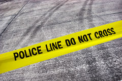 Street Crime Scene with Police Line Tape. Street crime scene with police line do not cross yellow warning tape above road with tire tracks royalty free stock photos