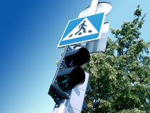 Street crossing. Street sign and semaphore of a pedestrian crossing place, clear blue sky overhead Stock Image
