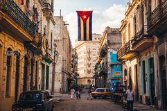 Street with Cuban flag in Havana. Havana, Cuba in December 2015: A cuban flag with holes waves over a street in Central Havana. La Habana, as the locals call it Stock Photography