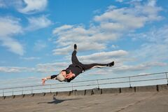 Street dancer hipster guy makes back flip with arm support on the roof outdoor.