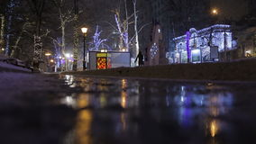 Street decorated for the Christmas celebration and reflection on a puddle. Street decorated for the Christmas and New Year celebration stock footage