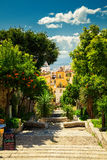 Street with descending steps in Taormina. Beautiful street with descending steps and orange trees in Taormina, Sicily Stock Images