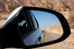 Street, desert and car seen from the rearview mirror stock photos