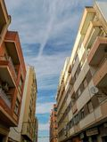 Street with different buildings in the Puerto de Sagunto. With cloudy sky royalty free stock photo