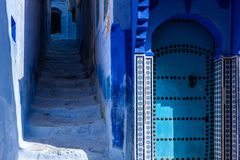 Chefchaouen, blue street and door, Morocco. Street and door of the old Medina of Chefchaouen, the Moroccan blue city royalty free stock photos