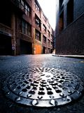 Street drain cover with golden sunlight in the background royalty free stock image