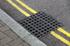 Street drain over Double yellow line on street Royalty Free Stock Image