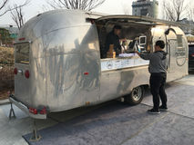 Street drinks in Seoul. SEOUL - MARCH 25, 2017: A man buys drinks at a street stall stylized from a retro steel house trailer, near the Dongdaemun History & stock photo