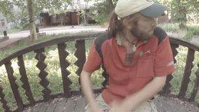 Street drummer plays hands on a makeshift drum on a wooden bridge in the park stock footage