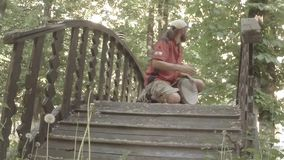 Street drummer plays hands on a makeshift drum on a wooden bridge in the park stock video