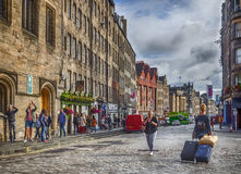 Street in Edinburgh Old Town. Woman pulling luggage suitcases and tourists on the street in the Edinburgh Old Town Stock Images