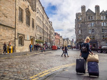 Street in Edinburgh Old Town. Woman pulling luggage suitcases and tourists on the street in the Edinburgh Old Town Stock Photography
