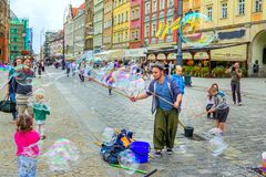 Street entertainer – playing with children, making soap bubbles. Wroclaw/Poland- August 19, 2017: young man – street entertainer – playing with children Stock Photography