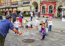 Street entertainer – playing with children, making soap bubbles. Wroclaw/Poland- August 19, 2017: young man – street entertainer – playing with children Stock Photos