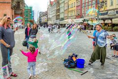 Street entertainer – playing with children, making soap bubbles. Wroclaw/Poland- August 19, 2017: young man – street entertainer – playing with children Stock Image