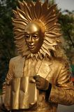 Street artist wearing a golden mask. Street entertainer in a golden mask and suit holding a open book Royalty Free Stock Photos