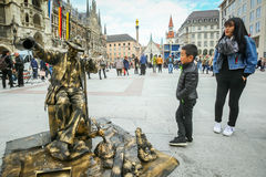 Street entertainer in Munich. MUNICH, GERMANY - MAY 9, 2017 : A boy and mother watching a street entertainer disguised as a sculpture fountain with people in the Stock Photography