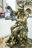 Street entertainer in Munich. MUNICH, GERMANY - MAY 9, 2017 : A street entertainer disguised as a sculpture fountain with people in the background sightseeing Royalty Free Stock Photos