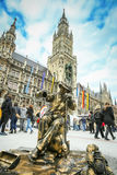 Street entertainer in Munich. MUNICH, GERMANY - MAY 9, 2017 : A street entertainer disguised as a sculpture fountain with people in the background sightseeing Stock Image