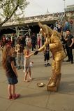 Street entertainer on the Southbank, London,UK. Street entertainer shaking the hand of a little girl as a thank you for donating some money Stock Photo