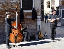Street Entertainers. This is a Fall picture of a trio of street entertainers performing on a street corner located in Venice, Italy. This picture was taken on stock photography