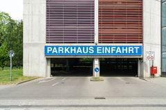 Entrance of a parking garage with the writen sign `Parkahsu Einfahrt` which means Parking garage entrance. Street and entrance of a parking garage with the royalty free stock images