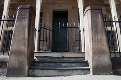Street entrance to old colonial building with wrought iron fence stock photography