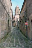 Street in Erice, Sicily - Italy. Alley in the city of Erice with the view of San Giuliano church tower Royalty Free Stock Photo