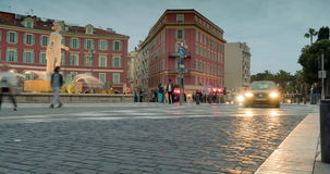 Street in european city. Town square in nice france. People cross the road at traffic signal. fountain in historic center. tram rides in the evening. time lapse stock video