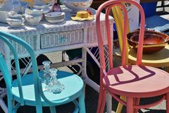 Street Fail Garage Sale Vintage Antique Dishes on Wicker Desk next to Colorful Wooden Brightly Painted Chairs Royalty Free Stock Photos