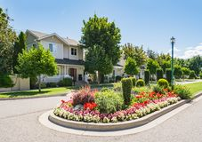 Street of family houses with elegant flowerbed on the road in front. Residential houses on a street with flower land on the road.  Family houses with elegant royalty free stock photos